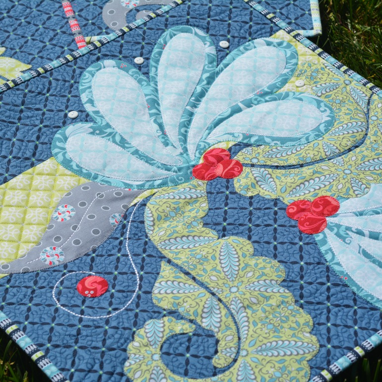 """Amanda's mini-quilt """"Flourishes"""", from her Feathers & Flourishes collection for Benartex, featuring blanket stitches in 28 wt. thread and triple-stitch stems in 12 wt."""