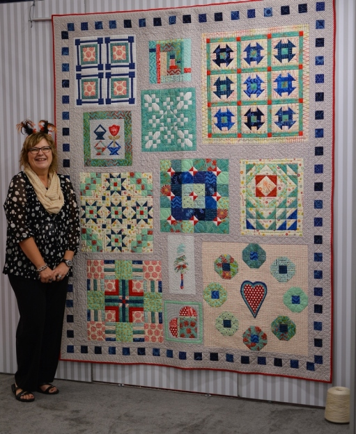 Pat posing with the 2015 Aurifil Designer of the Month Quilt