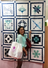 Wendy Sheppard pointing to her block int he 2016 Aurifil DOM Quilt