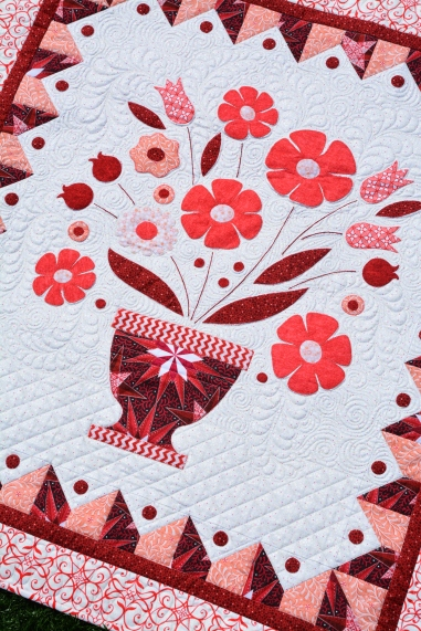 """Floret"" in red, featuring the Aurifil Celestial Lights thread collection."